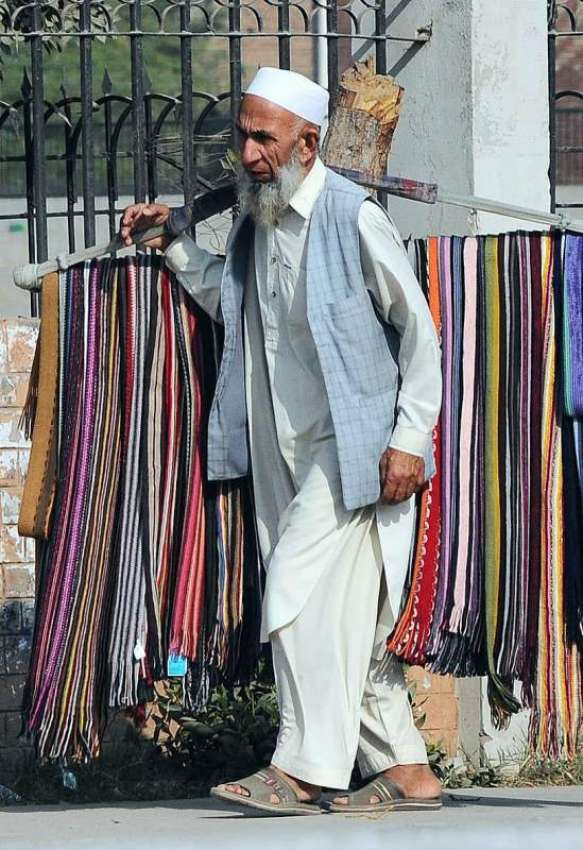 MULTAN An Elder Street Vendor Displaying Scarf To Attract The Customer While Shuttling On Abdali Road