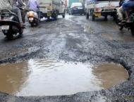 Rain-water filled deep potholes at Kahuta road make traffic movem ..