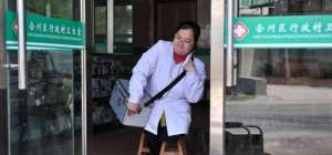 chinese lady doctor holds wooden stools against her leg