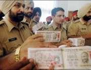 بھارتی پولیس اہلکار جعلی کرنسی نوٹ دکھا رہے ہیں، جو انکے مطابق کوئٹہ ..