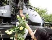 بینکاک، ایک تھائی خاتون سڑکوں پر موجود فوجیوں میں پھول تقسیم کر ..