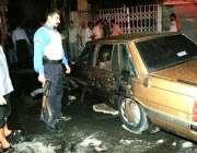 عراقی سکیورٹی اہلکار بم دھماکے میں تباہ ہونے والی گاڑی کا معائنہ ..