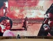 کراچی، ایک سنیما کے باہر مزدور فلم مغل اعظم کے بورڈ کی صفائی میں مصروف ..