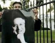 واشنگٹن، وائٹ ہائوس کے باہر ایک پاکستانی صدر مشرف کا پوسٹر اٹھائےکھڑا ..