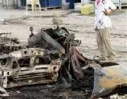 بغداد، ایک عراقی نوجوان خود کش حملے میں تباہ ہونے والی گاڑی کو حیرت ..