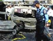 بغداد ،ایک سیکورٹی اہلکار خود کش حملے میں تباہ ہونے والی کاروں کے ملبے ..