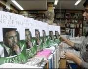 نئی دہلی، ایک بھارتی دوکاندار صدر مشرف کی کتاب کو شیلف پر رکھ رہا ہے۔