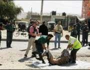 کابل، امدادی کارکن خود کش حملہ آور کی لاش سڑک سے اٹھا رہے ہیں۔