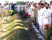 بالاکوٹ، مقامی لوگ ایک اجتماعی قبر پر کھڑے فاتحہ خوانی کر رہے ہیں، ..