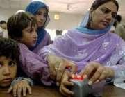 اسلام آباد، افغان مہاجرین کی رجسٹریشن کیلئے ایک  خاتون مشین پر اپنے ..