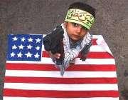 کراچی، امریکہ مخالف ریلی میں ایک بچہ کھلونا بندوق اٹھائے امریکی پرچم ..