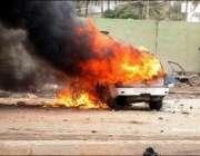 بغداد شہر میں کار بم دھماکے میں تباہ ہونے والی گاڑی کو آگ لگی ہوئی ہے۔