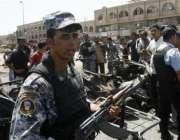 بغداد، عراقی سکیورٹی اہلکارخود کش کار بم دھماکے والی جگہ کی نگرانی ..