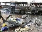 بغداد، ایک عراقی شہری کاربم دھماکے کے بعد تباہ شدہ گاڑیوں کے پاس کھڑا ..