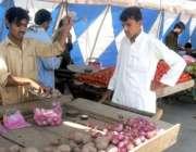 پشاور،ایک شخص رمضان المبارک کیلئے بنائے گئے سستے بازار سے سبزی خرید ..