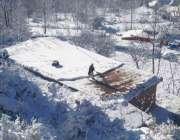 پوٹھی مکو الاں: برفباری کے بعد ایک شخص اپنے مکان کی چھت سے برف ہٹانے ..