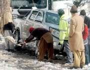 مری: برف میں پھنسی ایک گاڑی کے ارد گرد سے لوگ برف صاف کررہے ہیں۔