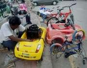 لاہور: ایک کارگر سڑک کنارے بچوں کی چھوٹی کاریں مرمت کر رہا ہے۔