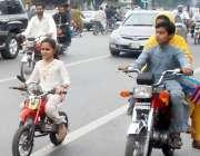 لاہور: ایک نو عمر بچی اپنی چھوٹی موٹر بائیک پر بیٹھی مال روڈ سے گزر رہی ..