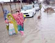 کوئٹہ ، بروری روڈپر بارش کا پانی کھڑا ہے، جسے خواتین اور بچے پار کرنے ..