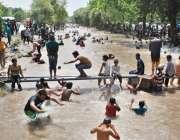 لاہور، گرمی کی شدت کم کرنے کیلئے شہری نہر میں نہا رہے ہیں۔