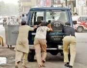 لاہور، مال روڈپر پولیس اہلکار اور شہری خراب گاڑی کو دھکا لگا رہے ہیں۔