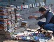 فیصل آباد، ایک طالبعلم سڑک کنارے لگے سٹال سے کتابیں خرید رہا ہے۔