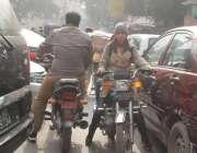 لاہور، ایک موٹر سائیکل سوار خاتون فین روڈ پر ٹریفک جام میں راستہ ملنے ..