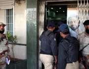کراچی، پولیس اور رینجرز اہلکار ڈکیتی کے بعد مقامی بینک کے باہر کھڑے ..