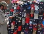 لاہور: ایک محنت کش ٹوپیاں فروخت کرنے کے لیے ترتیب سے لگا رہا ہے۔