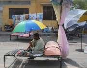 لاہور: ایک شخص چھتریاں اور مچھردانیاں فروخت کرنے کے لیے گاہکوں کا انتظار ..