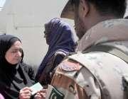 کراچی: حلقہ NA246کے ضمنی الیکشن کے موقع پر رینجرز اہلکار ایک خاتون کا ..
