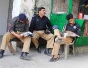 راولپنڈی: آصف علی زرداری کی پیشی کے موقع پر پولیس اہلکار اخبار کے مطالعہ ..