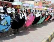 لاہور: ایک شخص نے علامہ اقبال موڑ کے قریب فٹ پاتھ پر چھتریوں اور ٹوپیوں ..
