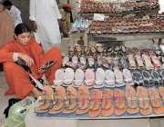 لاہور: ایک خاتون بادشاہی مسجد کے قریب لگے سٹال سے جوتا پسند کر رہی ہے۔