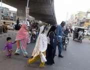 لاہور: ایک ٹریفک وارڈن فیروز پور روڈ پر سڑک عبور کرنے میں خواتین کی ..