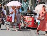لاہور: طالبات تیز دھوپ سے بچنے کے لیے چھتریاں تانے جا رہی ہیں۔