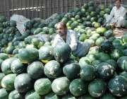 لاہور: ایک شخص گاہکوں کو متوجہ کرنے کے لیے تربوز سجا رہا ہے۔