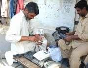 لاہور: دو کاریگر سڑک کنارے فٹ پاتھ پر بیٹھے ٹیلی فون مرمت کر رہے ہیں۔