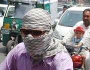 لاہور: ایک موٹرسائیکل سوار دوپہر کے وقت شدید گرمی میں لُو سے بچنے کے ..