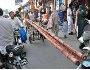 لاہور: ایک محنت کش ہتھ ریڑھی پر بانس رکھے جا رہا ہے۔
