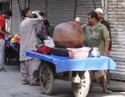 لاہور: ایک شخص گرمی کی شدت کم کرنے کے لیے ریڑھی والے سے لسی پی رہا ہے۔