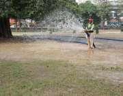 لاہور: پی اے اے کا ملازم ناصر باغ میں گھاس کو پانی لگا رہا ہے۔