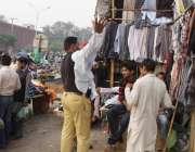 لاہور: ایک پولیس اہلکار لنڈا بازار سے کپڑے خرید رہا ہے۔