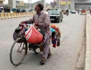 راولپنڈی: کار آمد کپڑے فروخت کرنیوالا ایک محنت کش مری روڈ سے گزر رہا ..