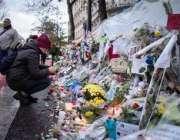 ایک خاتون پیرس حملہ میں ہلاک ہونے والے اپنے پیاروں کی یاد میں شمعیں ..