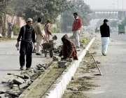 لاہور: جیل روڈ پر مزدور فٹ پاتھ تعمیر کر رہے ہیں۔