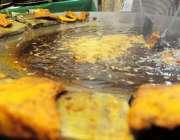 راولپنڈی: سردی میں مچھلی کی بڑھتی مانگ کے باعث ایک دکاندار مچھلی فرائی ..