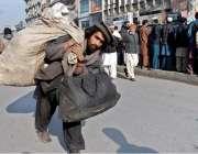 راولپنڈی: ایک محنت کش کار آمد اشیاء جمع کرنے کے بعد راجہ بازار سے گزرتے ..