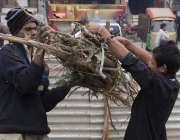 لاہور: دو شہری گھر کا چولہا جلانے کے لیے لکڑیاں اکٹھی کر کے باندھ رہے ..